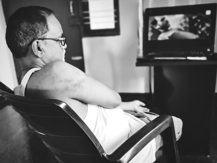 Midsection of man sitting at home