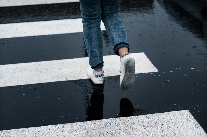 A girl in blue jeans and white sneakers crossing the zebra on a rainy day. Crossing The Road Crossing The Street Raindrops Shoe Backgrounds Casual Clothing Contrast Girl High Angle View Human Body Part Human Leg Jeans Legs Low Section Minimalism One Person Outdoors Personal Perspective Rainy Day Road Sneaker Walking Wet Zebra Crossing Zebra Stripes Fashion Stories