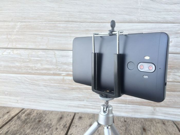 Close-up of smart phone on table against wall