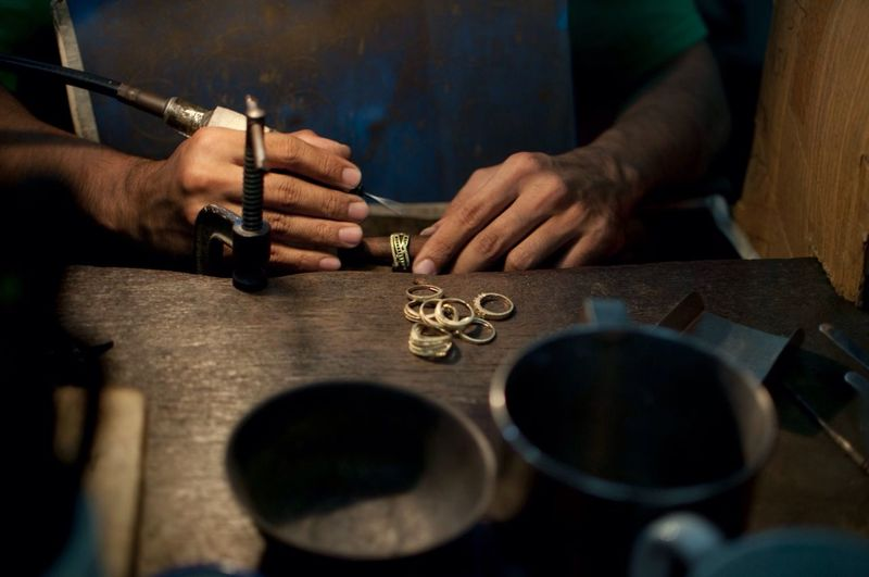 Midsection of man working at table in workshop