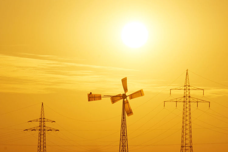 Low Angle View Of Windmill By Electricity Pylons Against Sky During Sunset