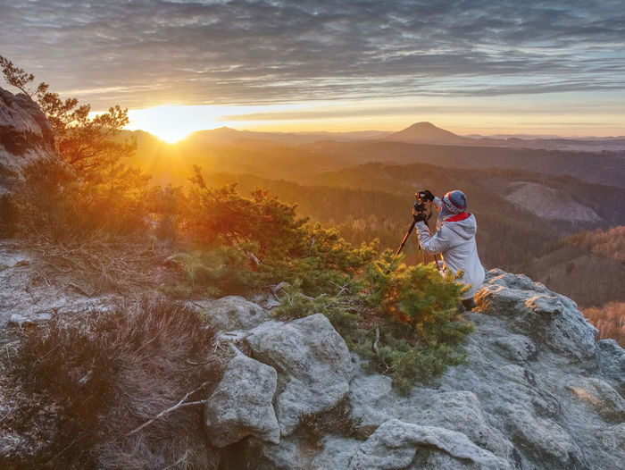 Woman hiker and photographer set tripod with camera on exposed rock above deep misty valley