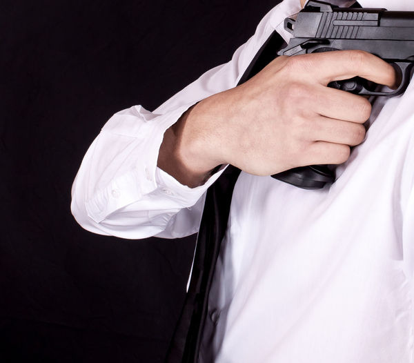 Midsection of man with handgun standing against black background