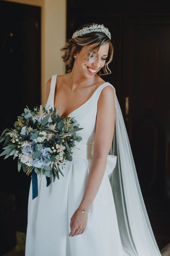 Bride holding bouquet standing against wall