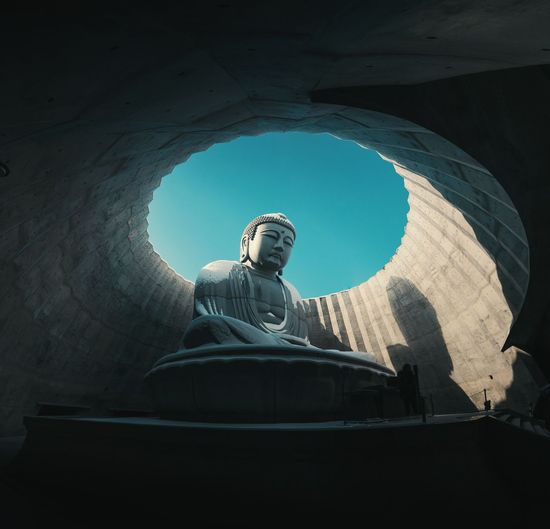 Low angle view of buddha statue in cupola against clear sky