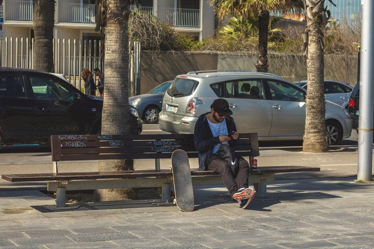 Full Length Sitting One Person City Bench Wireless Technology One Woman Only Outdoors Mature Adult People Communication Adults Only Adult One Young Woman Only Day Young Adult Snapshots Of Life Barcelona Portrait Of A City Skateboarding Skater Culture Beach Photography Sunlight Only Men
