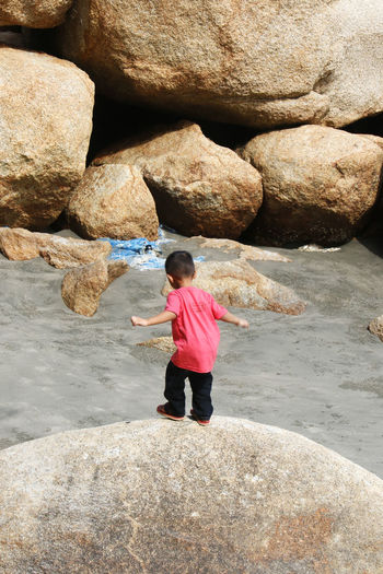 Rear view of boy standing on rock at beach