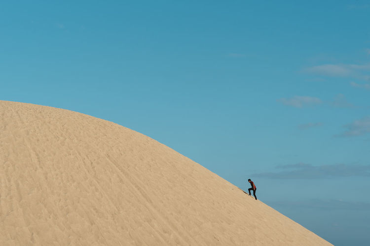 Man climbing on sand in desert against sky