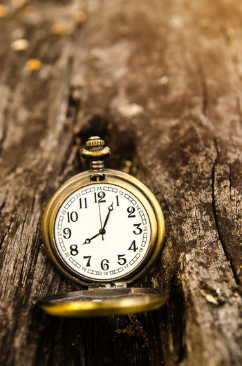 Close-up of a pocket watch on wooden table