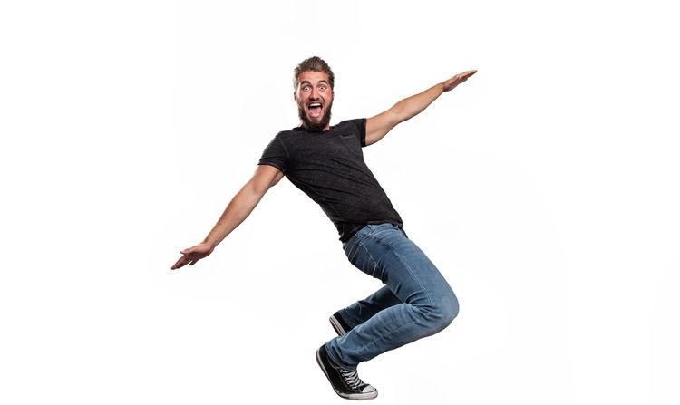 Portrait of an attractive man who is pretending to drive on a skateboard in front of a white background Active Activity Adult Balance Bearded Black Casual Clothing Caucasian Concept Full Length Fun Handsome Isolated Jeans Jumping Leisure Activity Lifestyles Movement People Portrait Scream Shirt Skateboard Sport White Background