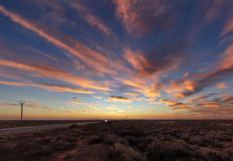 Desert Beauty In Nature Car Cloud - Sky Headlights Horizon Over Land Land Landscape Non-urban Scene Orange Color Scenics - Nature Sky