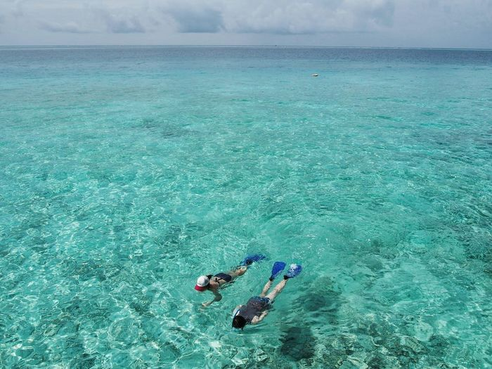 High angle view of people snorkeling in turquoise sea against sky