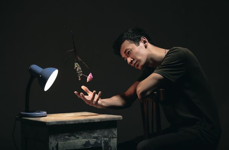 Man Sitting At Table With Illuminated Desk Lamp And Flower Against Black Background