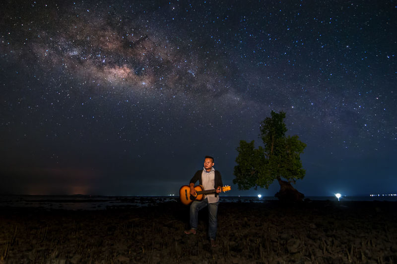 Man playing guitar while standing on land against sky at night