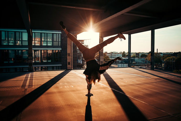 Full length of woman doing handstand indoors during sunset
