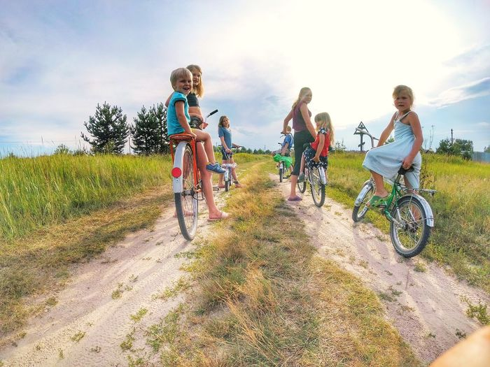 Cycling with friends and family Summertime Bike Kids Bysicle Summer Sports Friendship Young Women Full Length Togetherness Adventure Cycling Helmet Rural Scene Happiness Headwear Motocross Riding Cycling Empty Road Bicycle Moving Racing Bicycle