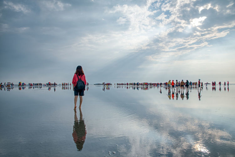 Rear view of woman standing by crowd at beach against sky