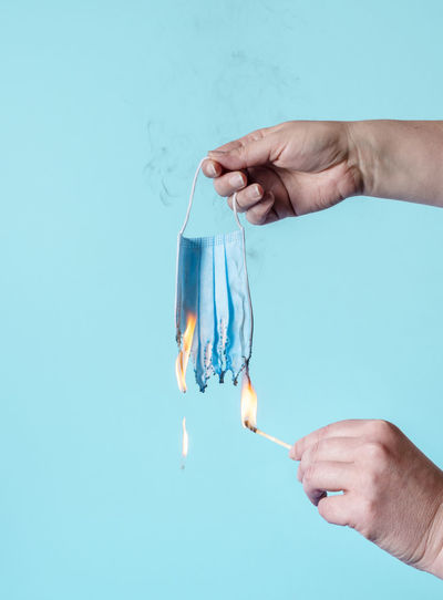 Midsection of person holding hands against blue background