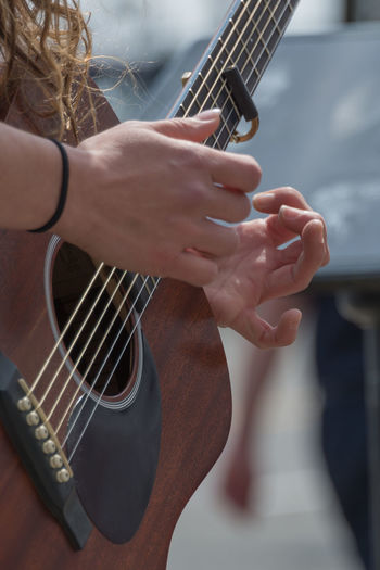 Cropped hands of woman playing guitar