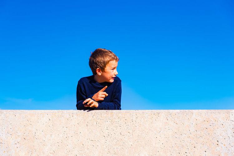 Boy looking away against blue sky