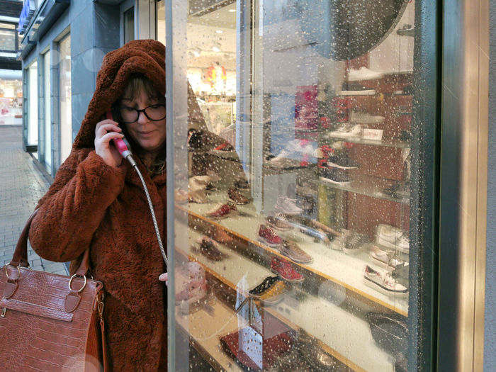 A woman is standing in the city, making a phone call from a payphone. it's raining. hoodie, glasses.