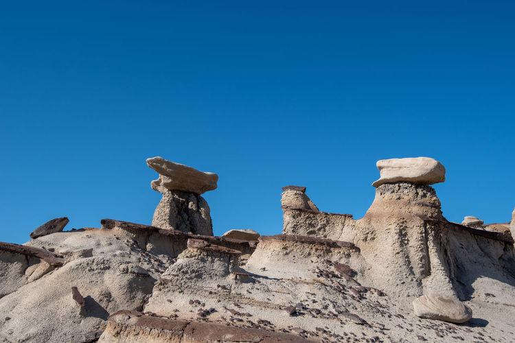 Bisti badlands landscape of dramatic grey hoodoos or caprock formations against blue sky