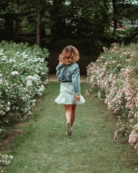 Rear view of woman walking on flowering plants
