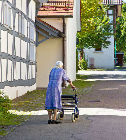 Old woman with Rollator Elderly Grandmother Old Woman Illness Old Woman Village Alone Care Health Care Insruance Time Rollator Disease Handicap Rheumatism Nursing Home Street City Outdoors People Senior Health Retirement Provision