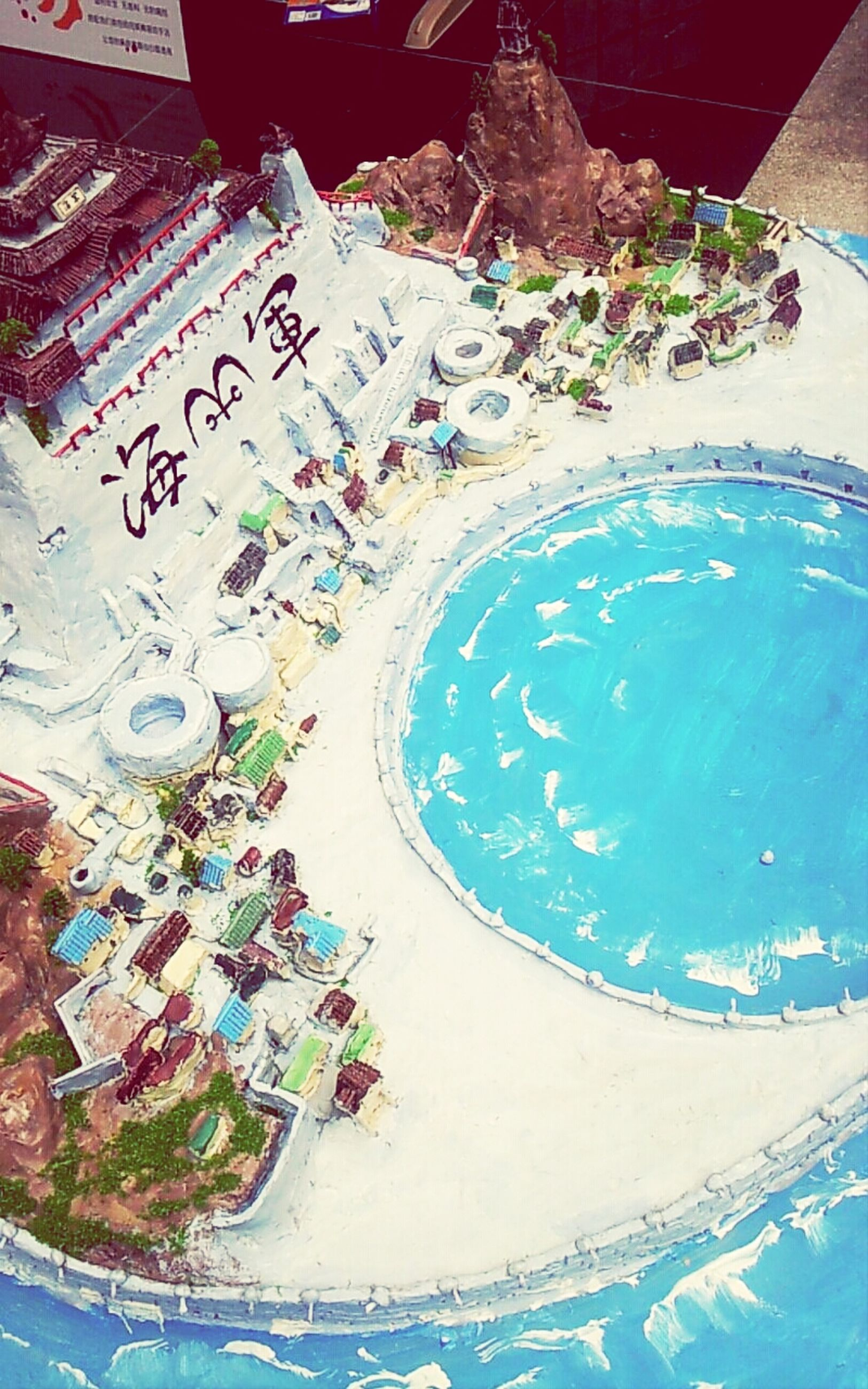 high angle view, text, water, blue, western script, communication, day, swimming pool, outdoors, street, no people, elevated view, sunlight, creativity, art, nature, close-up, art and craft, built structure, road