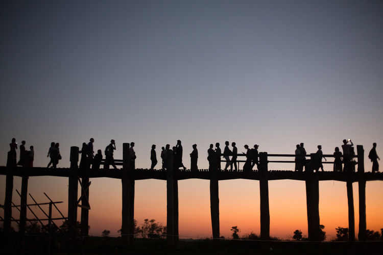 Silhouette people on bridge against clear sky during sunset