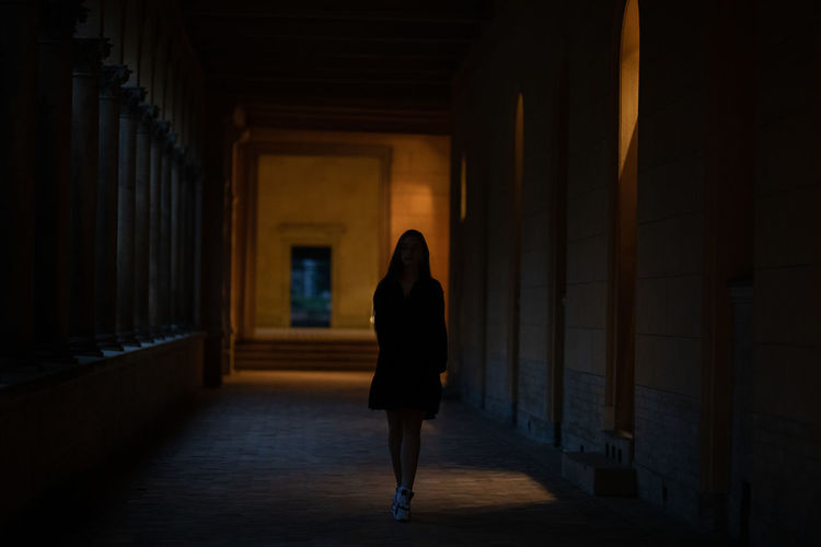 Woman walking in corridor of building