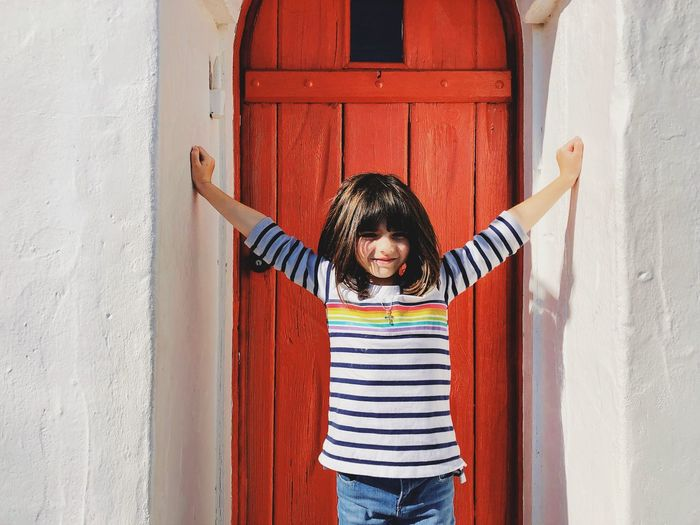Portrait of girl standing against door