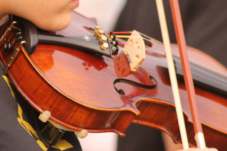 Midsection of woman playing violin at event