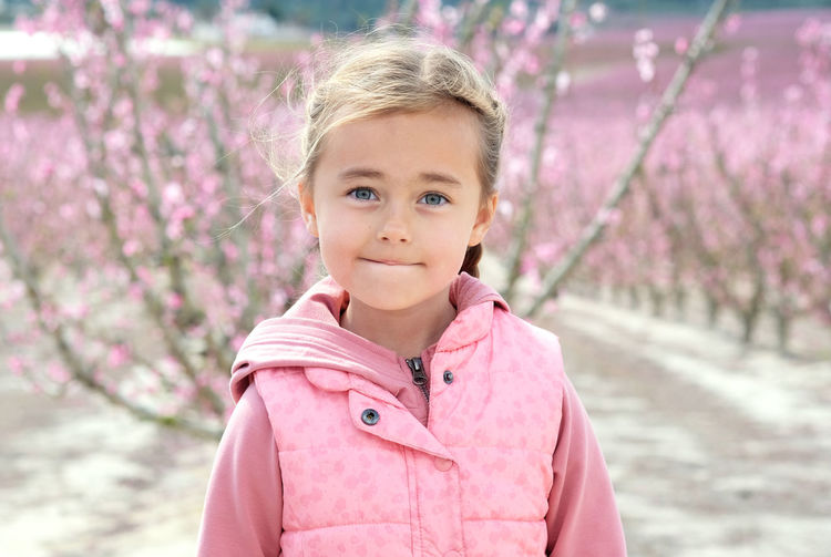Portrait of cute girl standing against cherry trees
