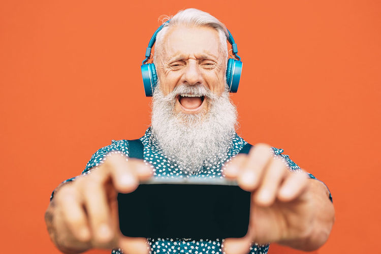 Hipster senior man taking selfie person Hipster Senior Adult Senior Man Beard Pensioner Retirement Happy Technology Wireless Technology One Person Front View Men Males  Communication Portrait Holding Smart Phone Headshot Facial Hair Adult Lifestyles Mobile Phone Mouth Open