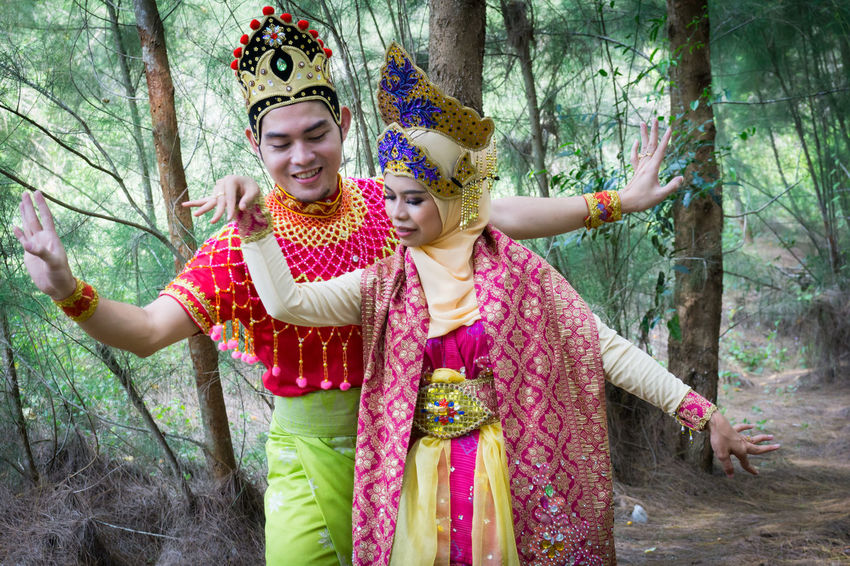 Specific to the villages of Kelantan, where the tradition originated, Mak Yong is performed mainly as entertainment or ritual purposes by couple of dancers. Celebration Day Forest Front View Happiness Holding Human Hand Lifestyles Mak Yong Nature One Person Outdoors People Playing Real People Smiling Standing Tree Tree Trunk Young Adult Young Women