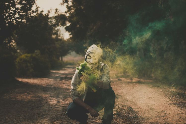Portrait of man wearing mask while holding distress flare on dirt road amidst trees