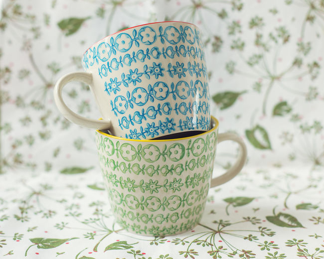 Blue and green floral teacups on placemat with green leaves Breakfast Drinking Tea Home Morning TeaCup Blue Ceramics Crockery Cup Drink Floral Pattern Green Color Hot Drink Indoors  Leaves Pattern Mug No People Porcelain  Still Life Tea Tea Cup Tea Time