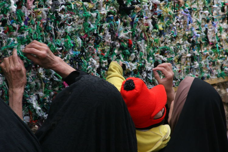 Women tying fabric on wall
