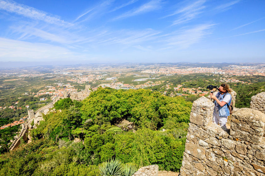 Photographer with stabilizer and professional camera takes photos at Sintra Valley from Castle of Moors. Moorish fortress is medieval castle and Unesco Heritage on top of a hill above Sintra, Portugal Portugal Sintra Castle Ruins Medioeval Cities Wall Tourism Flags Skyline Cityscape Palace Castle Ruin Aerial View Man Photography Moors Castle Pena Palace Moors Two People Nature Leisure Activity Architecture Sky Men Landscape Environment Scenics - Nature Togetherness Adult Mountain Day People Couple - Relationship Plant Tree Heterosexual Couple Hiking Travel Destinations Outdoors Positive Emotion
