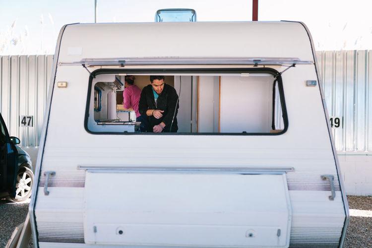 Couple seen through window of camper trailer