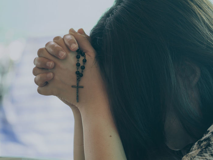 Close-up of woman holding rosary beads and praying