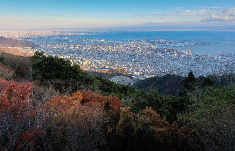 """View of several Japanese cities in the Kansai region from Mt. Maya. The view is designated a """"Ten Million Dollar Night View."""" Autumn Observation Point Architecture Bay Beauty In Nature City Cityscape Cloud - Sky Day Growth High Angle View Landscape Mountain Mountain Range Nature No People Ocean Outdoors Scenics Sky Tranquil Scene Tranquility Travel Destinations Tree Viewpoint"""