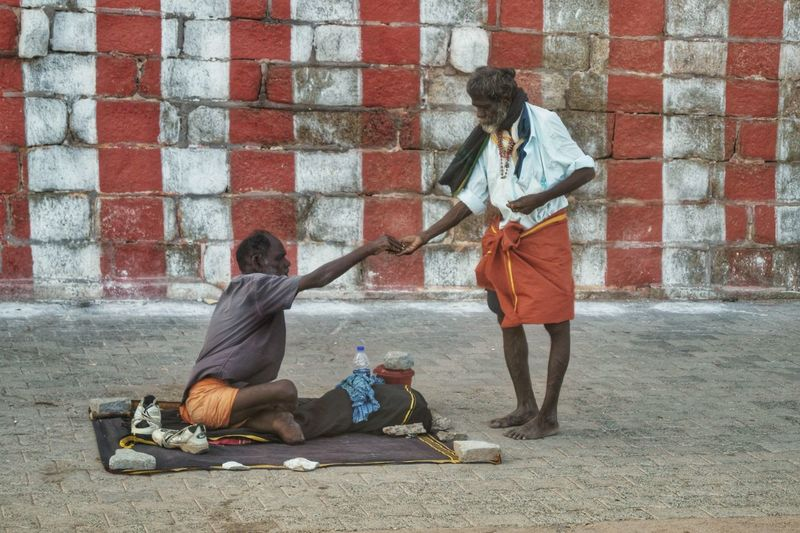 Man giving money to beggar on street against wall