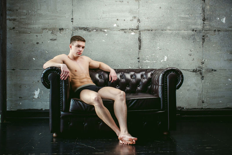 Shirtless Muscular Man Sitting On Armchair By Wall