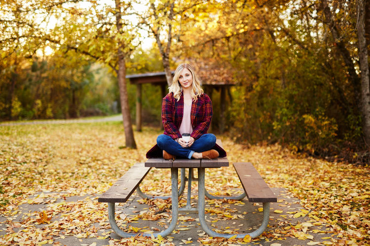 Adult Autumn Beautiful Woman Blond Hair Change Cheerful Day Forest Full Length Leaf Leisure Activity Long Hair Nature One Person One Woman Only One Young Woman Only Only Women Outdoors Park - Man Made Space People Sitting Smiling Tree Young Adult Young Women