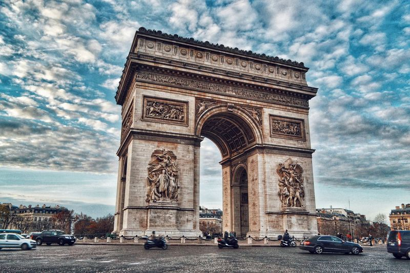 Low angle view of triumphal arch against cloudy sky