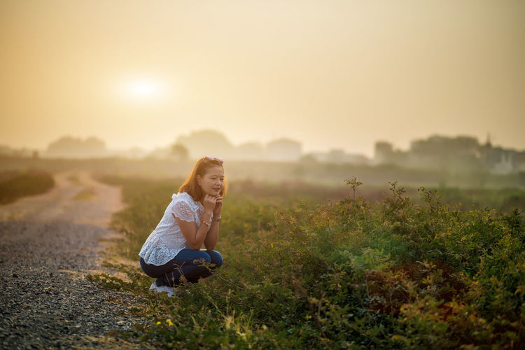 Woman crouching on field against sky during sunset