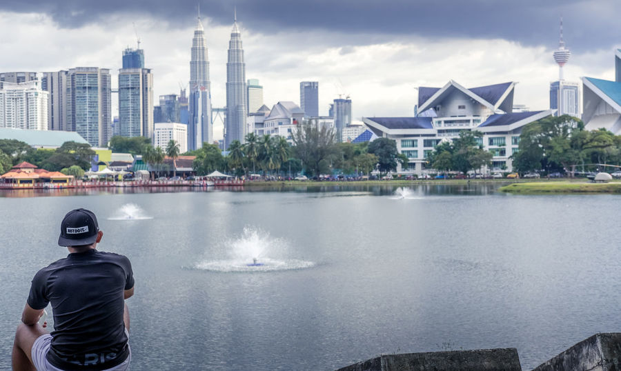 A Malaysian man sitting on a rock, enjoying the skyline view of Kuala Lumpur, Malaysia Cityscape Kuala Lumpur Kuala Lumpur Malaysia  Kuala Lumpur Twin Tower Skyline Architecture Building Exterior Built Structure City Day Kuala Lumpur City Center Leisure Activity Lifestyles Malaysian People One Person Outdoors People Petronas Twin Towers Real People Sky Skyscraper Twin Towers Water