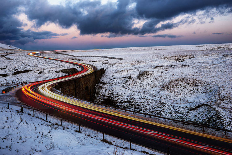 Light trails through the snow Beauty In Nature Car Cloud - Sky Day High Angle View Illuminated Land Vehicle Light Trail Mode Of Transport Motion Nature No People Outdoors Red Road Sky Speed Transportation Winding Road Fresh On Market 2018